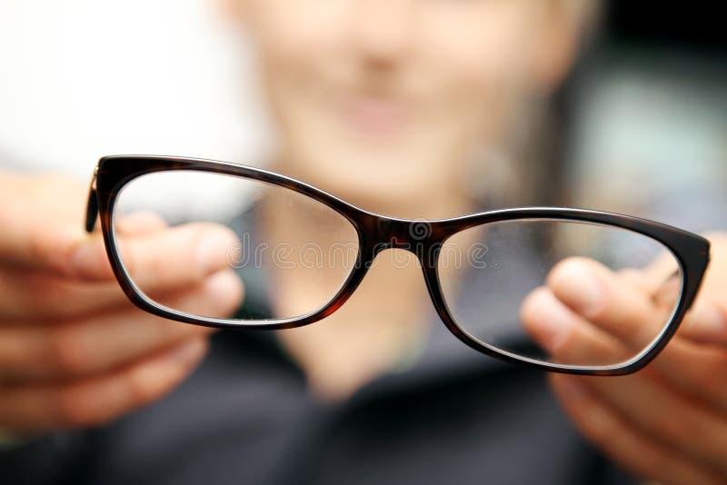 Eyeglasses λαβής χεριών γυναικών μπροστά από την στοκ φωτογραφία με δικαίωμα ελεύθερης χρήσης