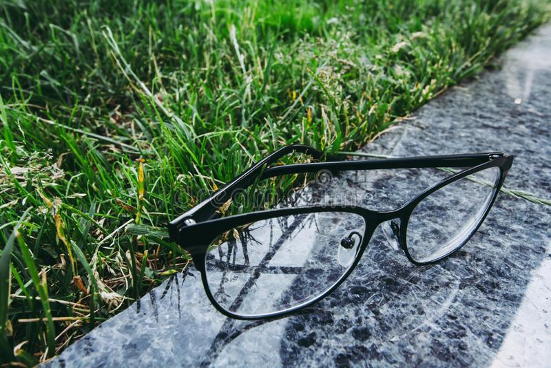 Eyeglasses μαύρο πλαισίων στην επιφάνεια γρανίτη κοντά στη χλόη στοκ εικόνες