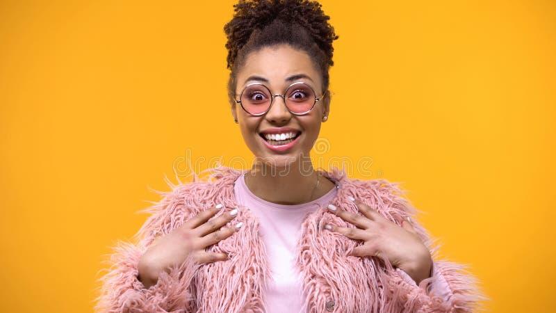 Изумленная стильная женщина в розовых eyeglasses смотря камеру, выражение ободрения стоковое изображение