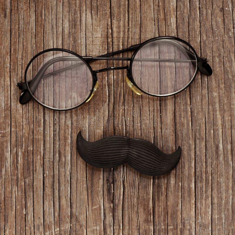 Eyeglasses и усик на деревянной поверхности стоковое изображение rf