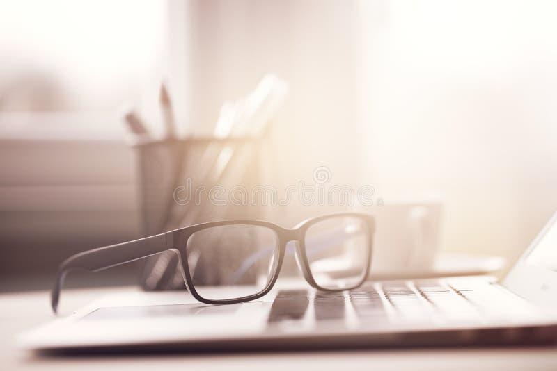 Eyeglasses на компьтер-книжке в солнечном свете стоковое изображение