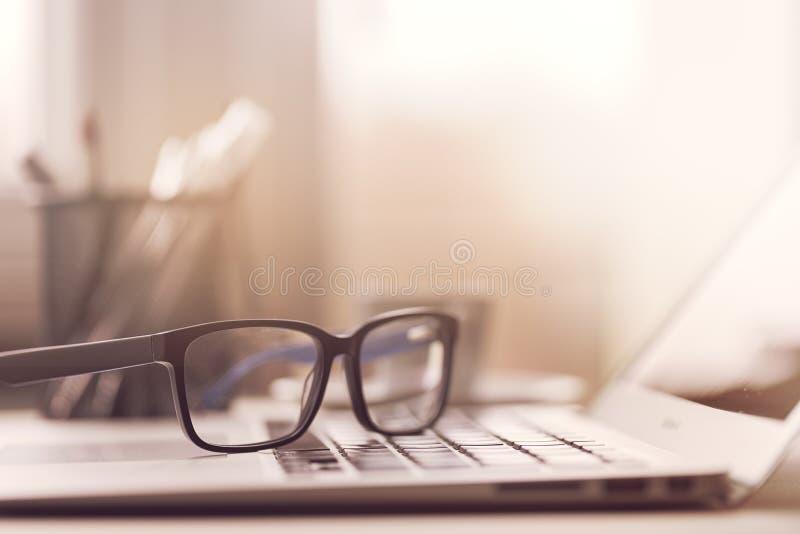 Eyeglasses на компьтер-книжке в солнечном свете стоковая фотография