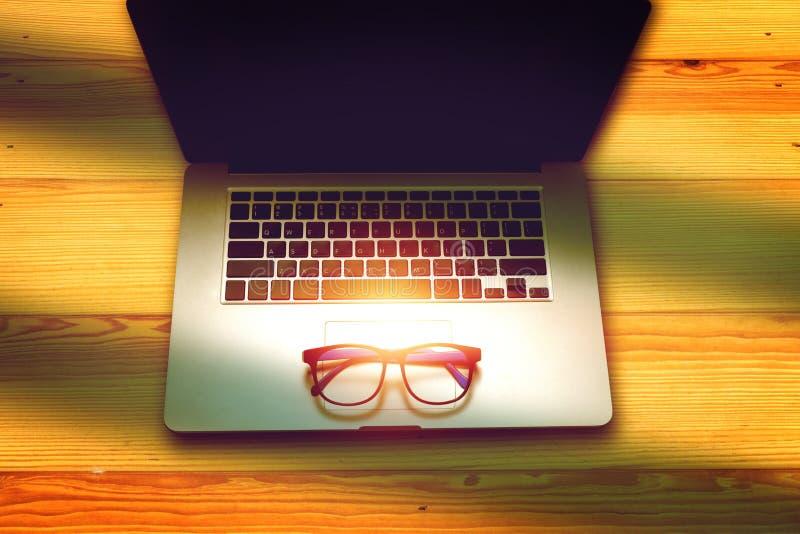 Eyeglasses на портативном компьютере на деревянном столе стоковые фотографии rf