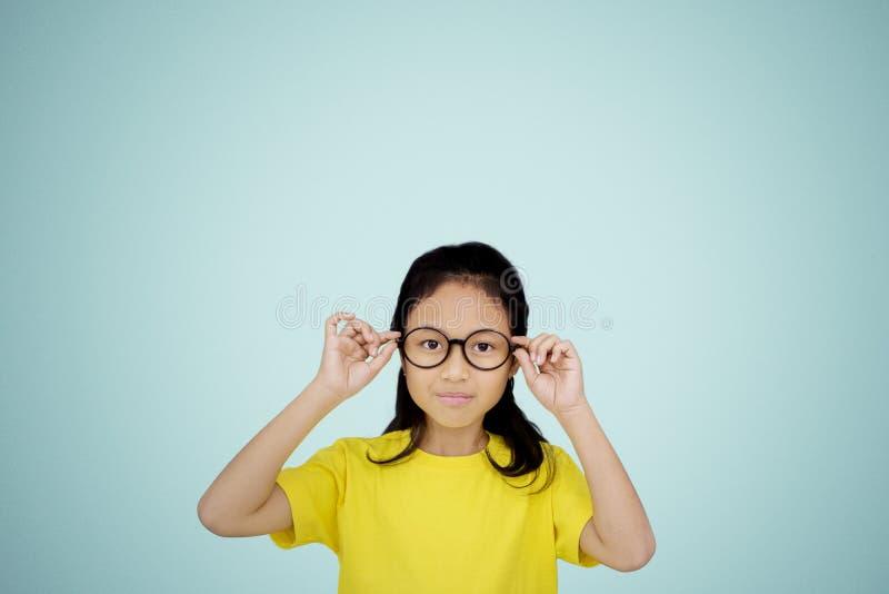 Eyeglasses уверенной маленькой девочки нося на студии стоковое фото