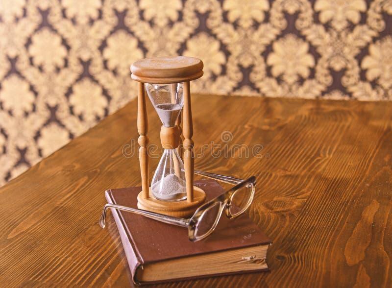 Часы, старая книга и eyeglasses на деревянном столе, предпосылке картины Песок падая вниз внутрь часов Премудрость стоковые фотографии rf