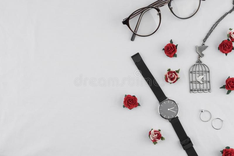 Eyeglasses, black watches, necklace and rings stock photo