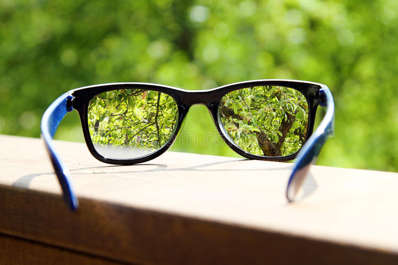 Eyeglasses in the hand over blurred background. Eyeglasses in the hand over blurred tree background stock photos