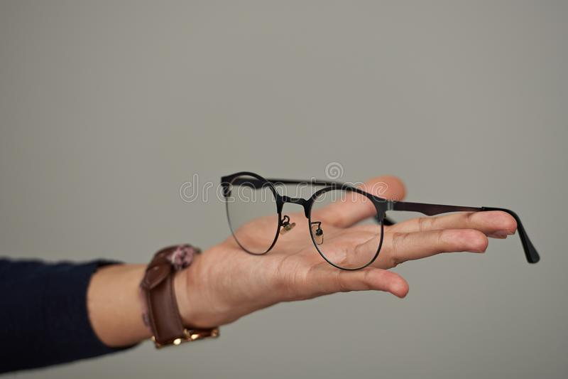 Eyeglasses on human palm stock photo