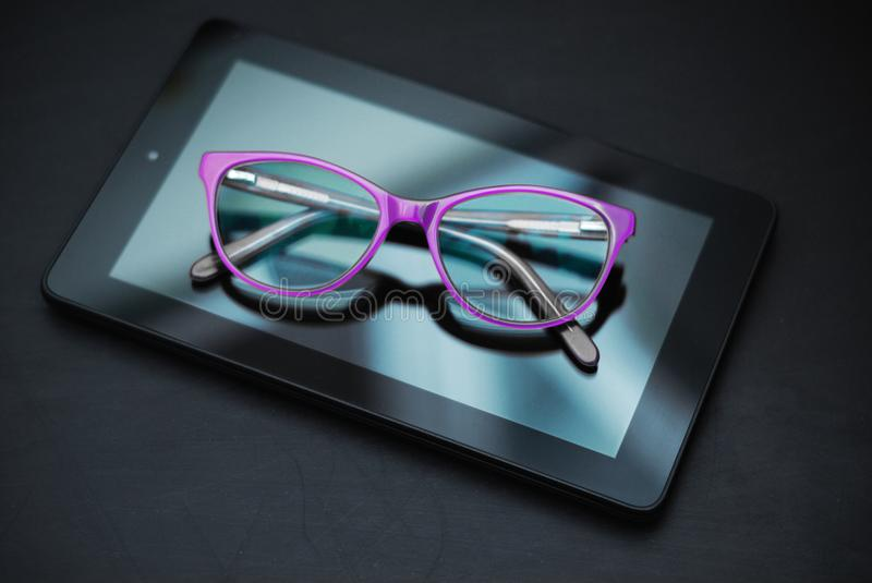 Eyeglasses on Ipad and Mobile Phone over Dark Background with copy space. Education, technoogy, internet. Eyeglasses on Ipad and Mobile Phone over Dark royalty free stock photos