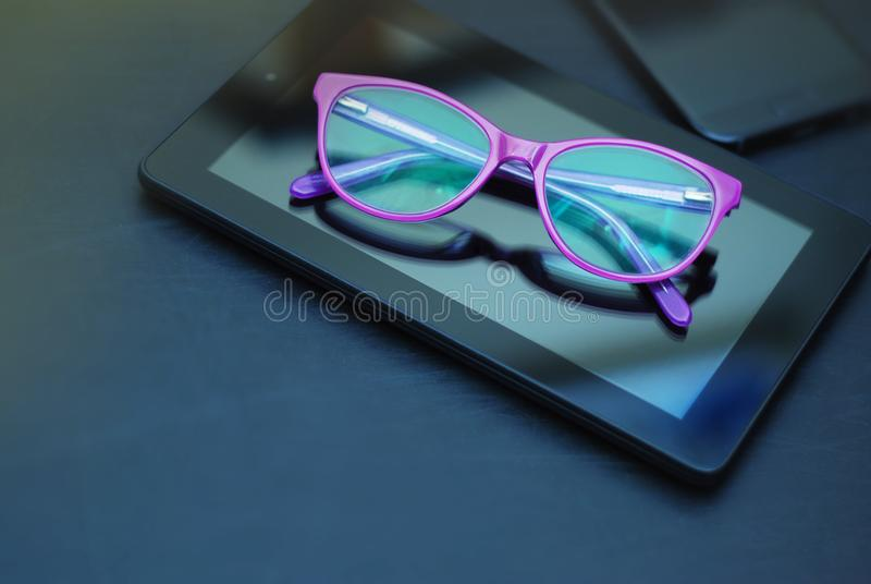 Eyeglasses on Ipad and Mobile Phone over Dark Background with copy space. Education, technoogy, internet. Eyeglasses on Ipad and Mobile Phone over Dark stock images