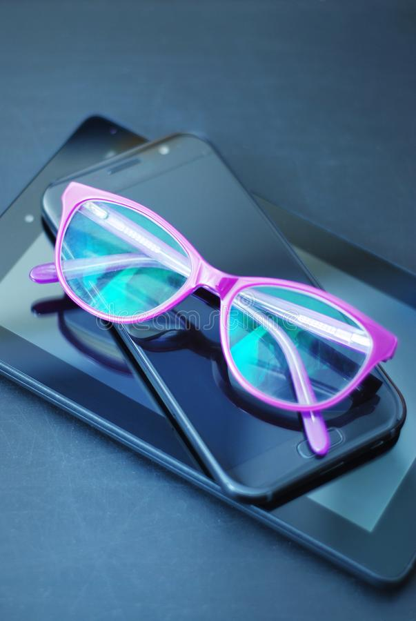 Eyeglasses on Ipad and Mobile Phone over Dark Background with copy space. Education, technoogy, internet. Eyeglasses on Ipad and Mobile Phone over Dark stock photo