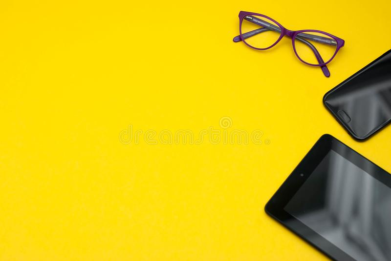 Eyeglasses on Ipad and Mobile Phone over Yellow Background with copy space. Education, technoogy, internet. Eyeglasses on Ipad and Mobile Phone over Yellow stock photos