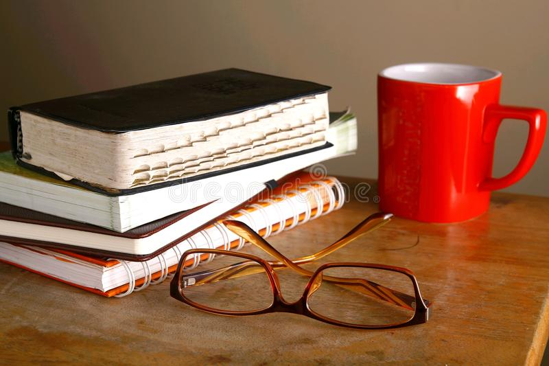 Eyeglasses, kawowy kubek i stos książki, obraz royalty free