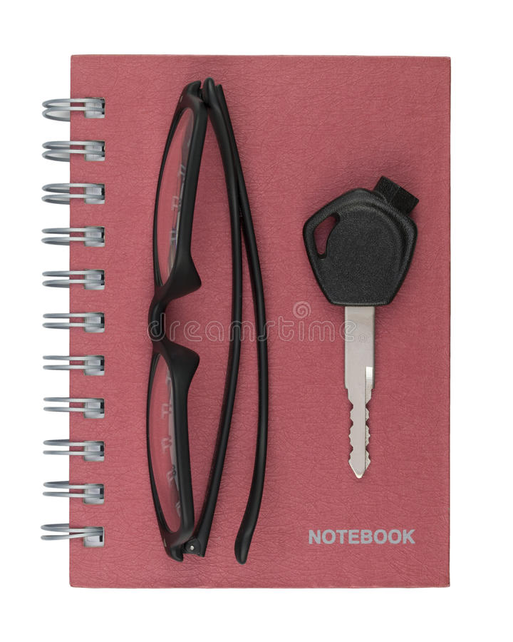 Eyeglasses and key place on red notebook on white background. stock photography