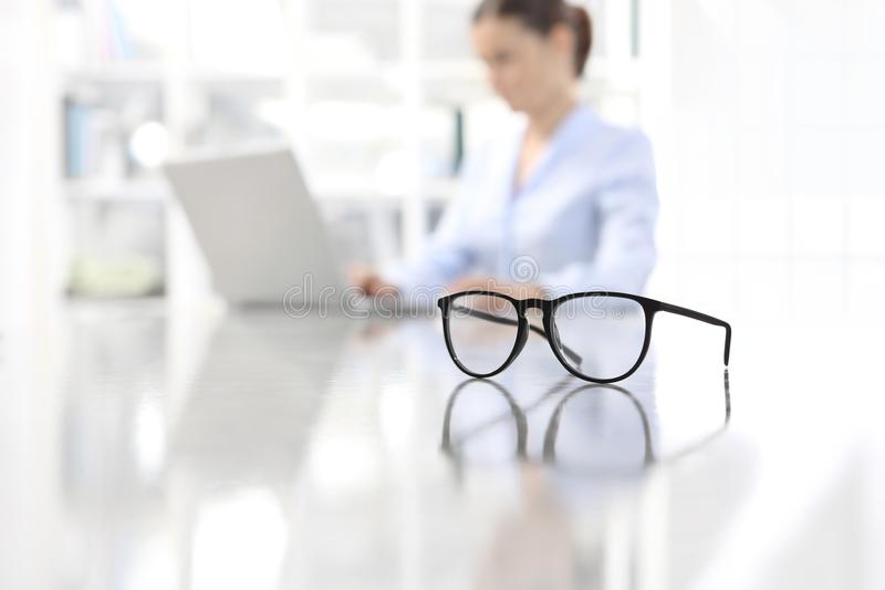 Eyeglasses leaning on desk and woman working on computer at offi royalty free stock images