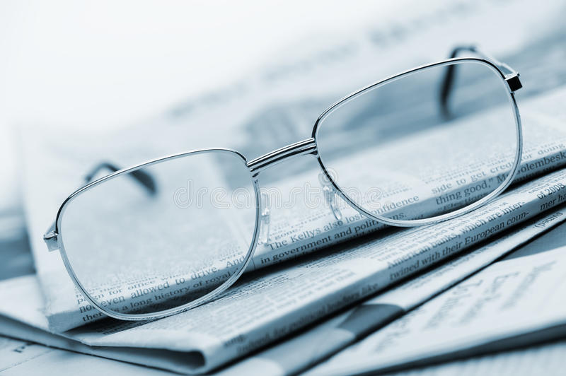 Download Eyeglasses Lie On A Pile Of Newspapers.Blue Toned Stock Photo - Image: 22185368