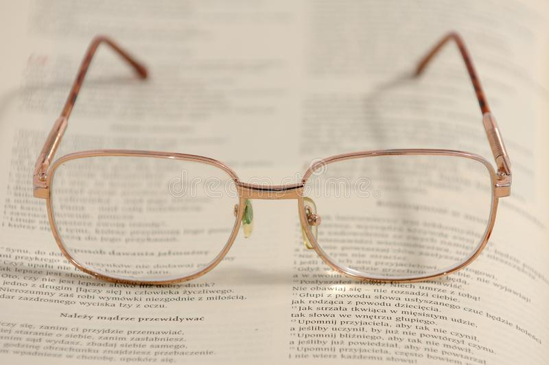 Eyeglasses lying on an old book. The New Testament royalty free stock photo