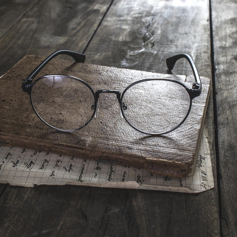 Eyeglasses and old book stock photos