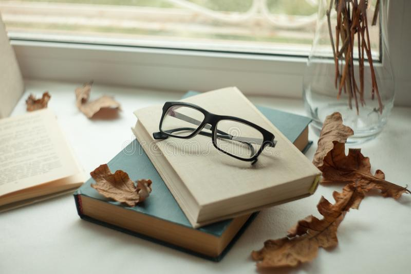 Eyeglasses and open book with autumn leaveson wooden table.Autumn mood concept.  royalty free stock images