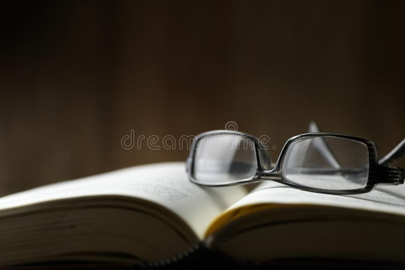 Eyeglasses on open book, education concept. And dark tone stock photography