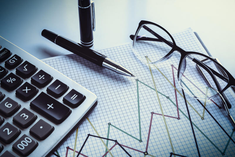 Eyeglasses and pen on financial document with data stock image