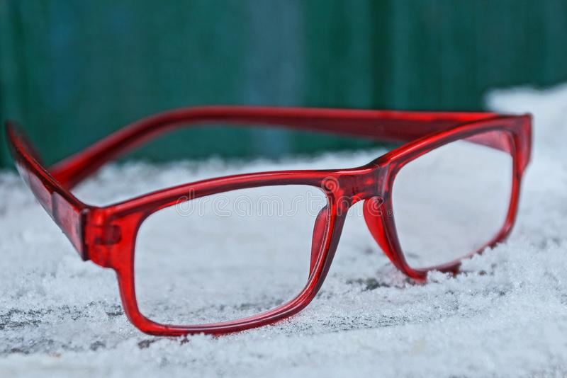 Eyeglasses with red frames on a table in white snow royalty free stock photography