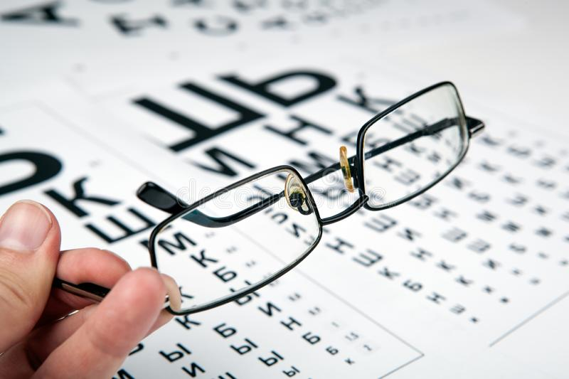 Eyeglasses on the table with a font to determine of eyesight Russian version. Eyeglasses on the table with a font to determine of eyesight Russian stock photography