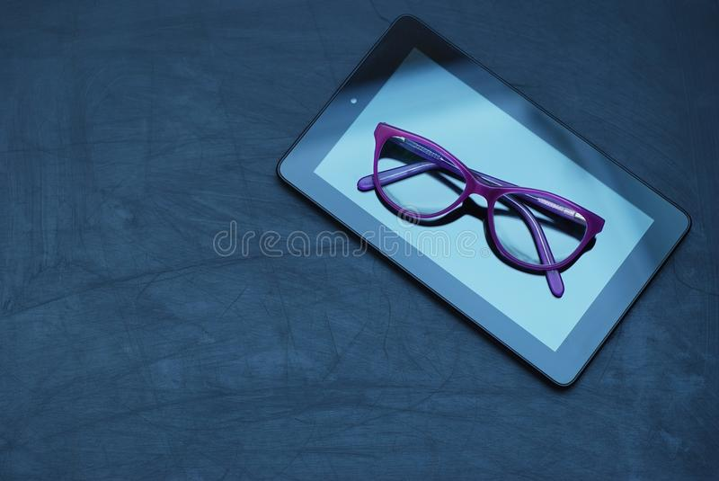 Eyeglasses on Tablet and Mobile Phone over Dark Background with copy space. Education, technoogy, internet. Eyeglasses on Tablet and Mobile Phone over Dark stock photos