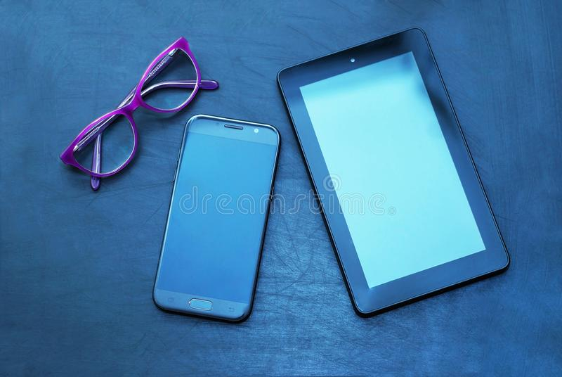 Eyeglasses and Tablet and Mobile Phone over Dark Background with copy space. Education, technoogy, internet. Eyeglasses Tablet Mobile Phone over Dark Background royalty free stock images