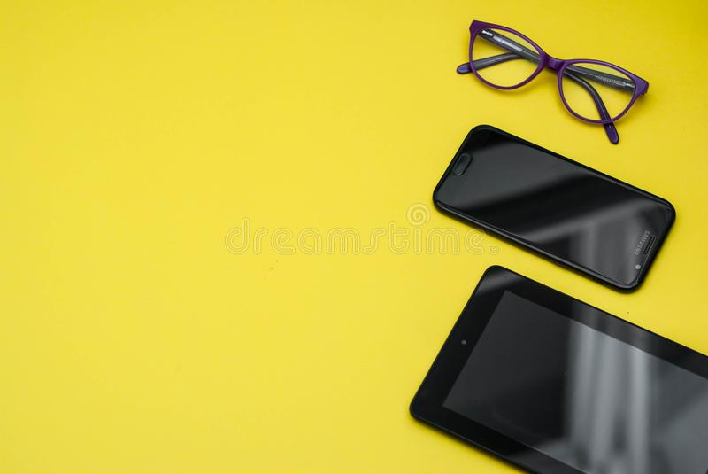 Eyeglasses on Tablet and Mobile Phone over Yellow Background with copy space. Education, technoogy, internet. Eyeglasses on Tablet and Mobile Phone over Yellow stock image