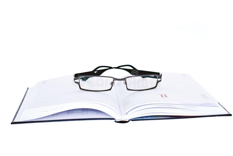 Eyeglasses on top of agenda stock image