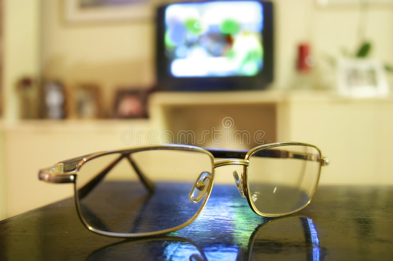 Eyeglasses and tv set stock images