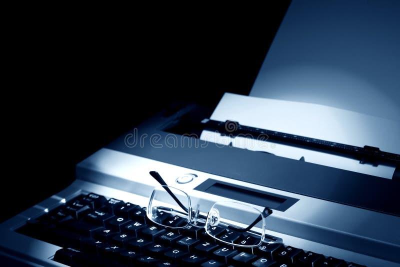 Eyeglasses On Typewriter. Eyeglasses on keyboard of electric typewriter with blank paper stock photos