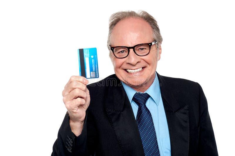 Eyeglasses vestindo do ancião que sustentam um cartão de dinheiro fotos de stock