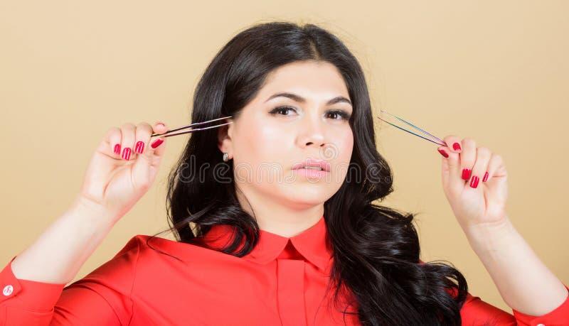 Προσωπική φροντίδα e όμορφα τσιμπιδάκια λαβής γυναικών eyelash κύρια επαγγελματικό beautician στο σαλόνι ομορφιάς στοκ εικόνες