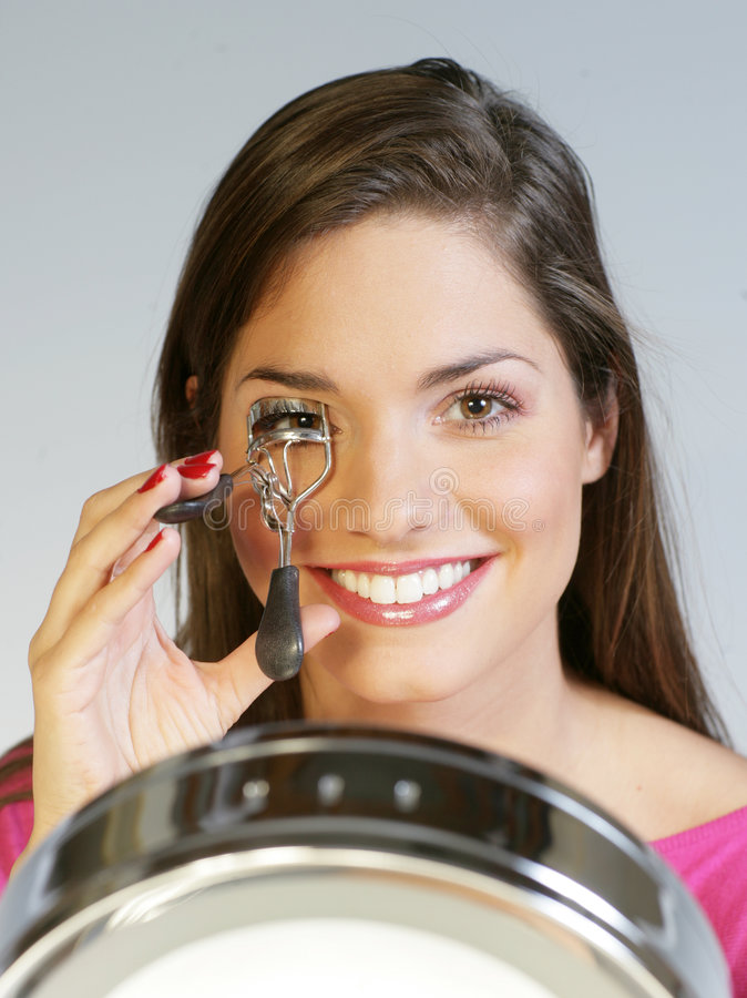 Eyelash curler. A young pretty woman with a lash curler and a mirror royalty free stock photos