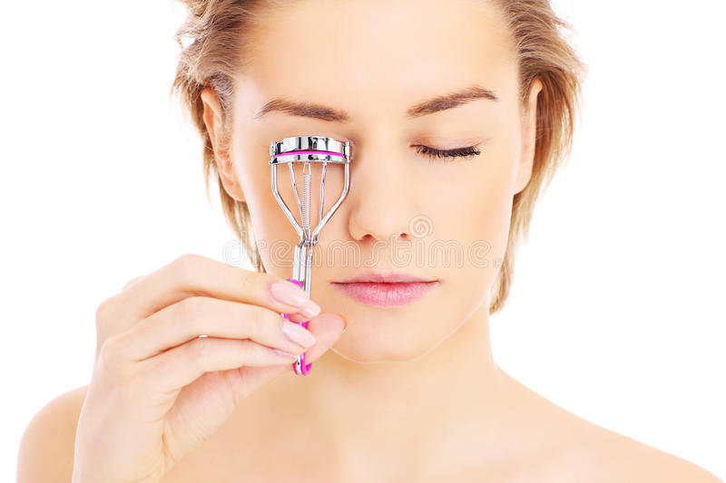 Eyelash curler. A picture of a young pretty woman posing with eyelash curler over white background stock photography