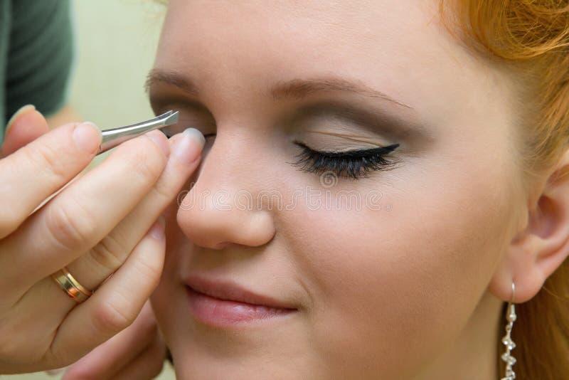 Eyelash extension. Beautiful young model getting fashion make-up and eyelash extension stock photo