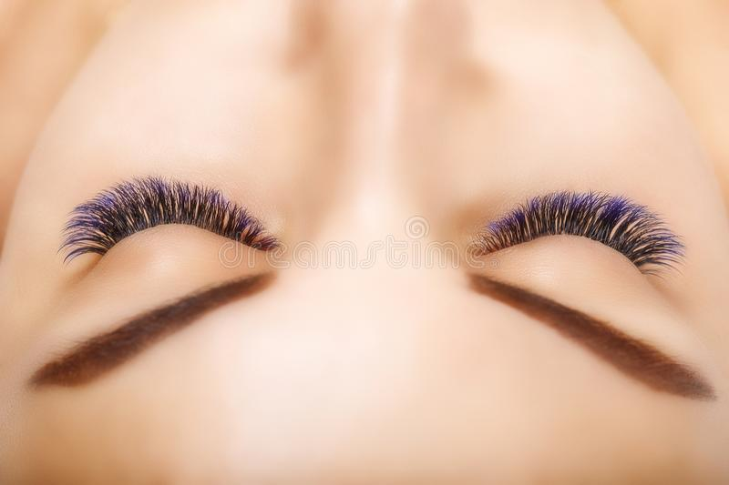 Eyelash Extension Procedure. Woman Eye with Long Blue Eyelashes. Ombre effect. Close up, selective focus. Eyelash Extension Procedure. Woman Eye with Long royalty free stock photos