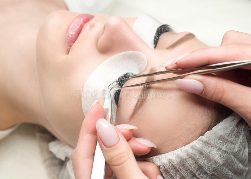 Eyelash extension procedure. Woman face and experts fingers with tweezers, close up, selective focus stock photo