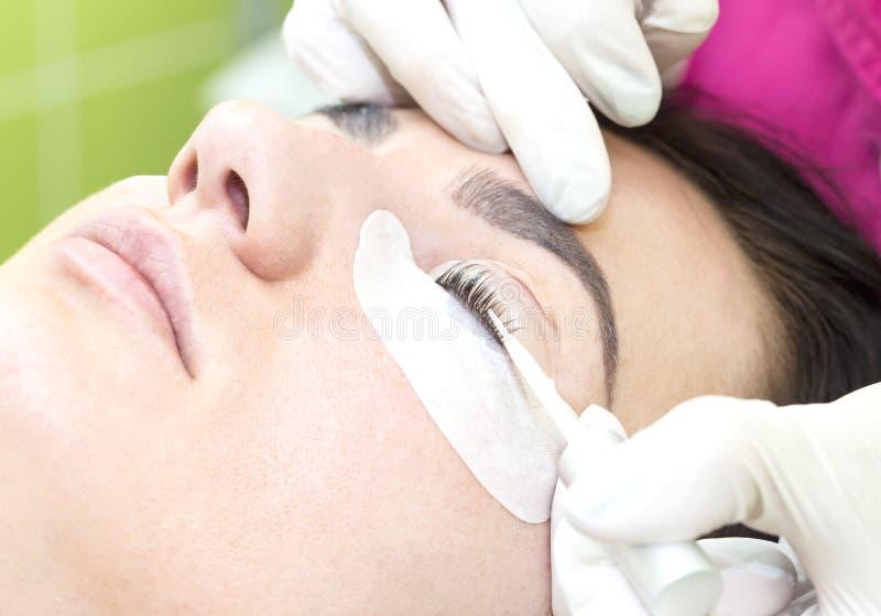 Eyelash extensions, eyelashes lamination. Woman on the procedure for eyelash extensions, eyelashes lamination royalty free stock photography