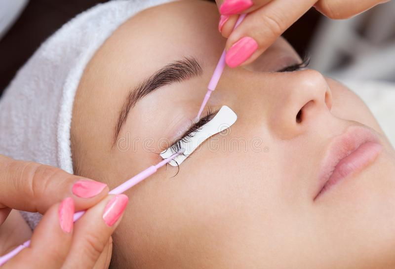 Eyelash removal procedure close up. Beautiful Woman with long lashes in a beauty salon. Eyelash extension royalty free stock images