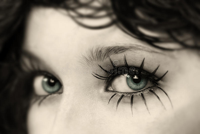 EyeLashes. Close up to spider eyelashes, specially focused on left eye and bronze glimmer glass lens filter used to emphasize model's eye color in studio shot stock photography