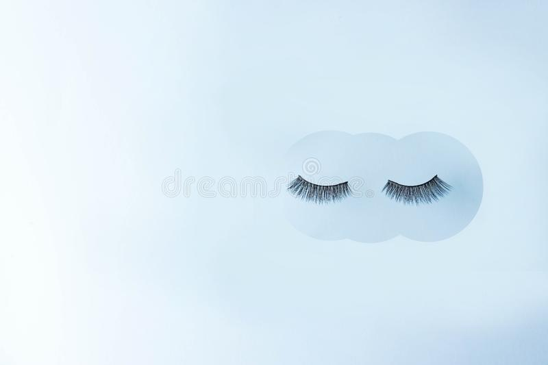 Eyelashes on blue background, copy space. concept of beauty stock photography
