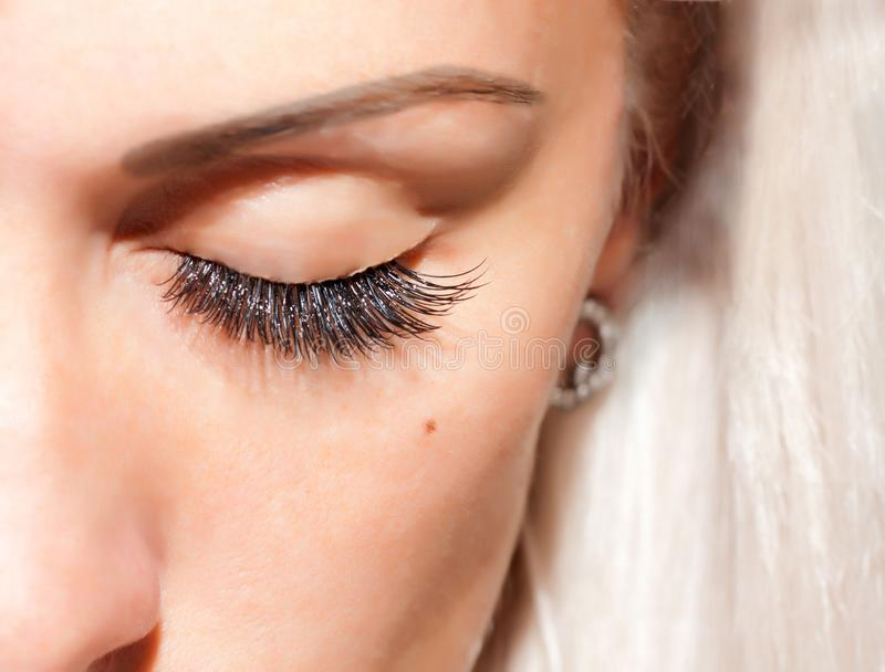 The eyelashes extensions. A woman`s face, eyes with long, black, extended eyelashes royalty free stock photos