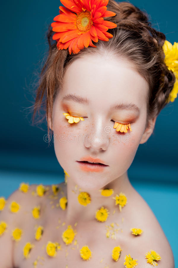 Eyelashes like petals of flowers. Beautiful young girl in the image of flora, close-up portrait royalty free stock photo