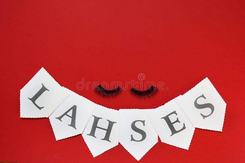 Eyelashes op rode achtergrond met exemplaarruimte, schoonheidsconcept stock afbeelding