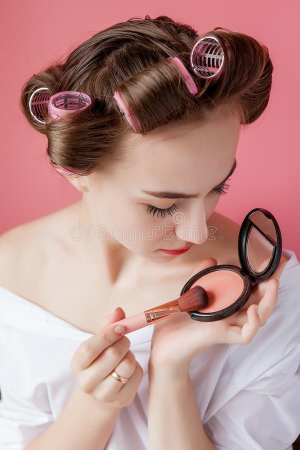 Eyeliner eye makeup beauty care woman. Girl putting eye pencil color on eyes looking in a pocket mirror smiling happy on pink stock image