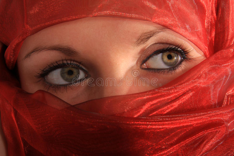 Eyes. Young woman with red veil royalty free stock photography