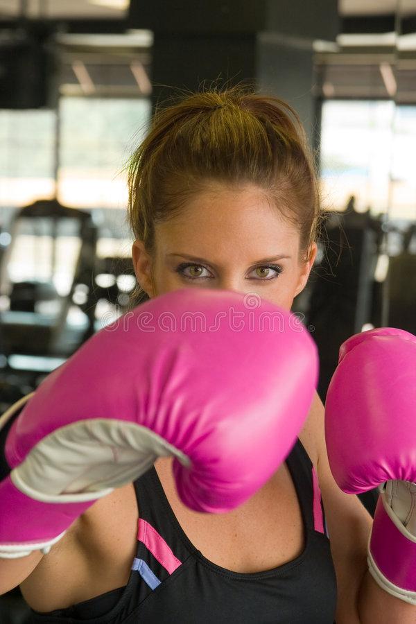 Eyes Above Pink Boxing Gloves 1. Eyes of beautiful woman looking over hot pink boxing gloves stock photography